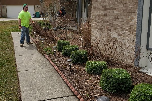 A member of the Priority One Lawn care team in the process of cleaning up a landscape bed.